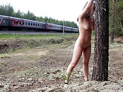 Tied girl to the tree, near the passing train.